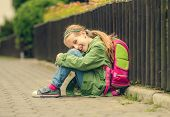 stock photo of schoolgirls  - Little pretty schoolgirl  sitting on the street with her backpack - JPG