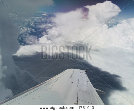 Shot Of An Airplane Wing Flying Over Clouds In A Dark Blue Sky