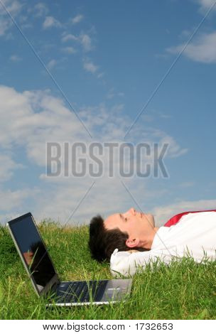 Businessman Lying On The Grass With Laptop