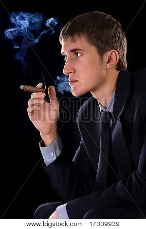 young smoking man with cigar on black background