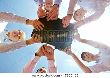 Below angle of businesspeople holding black leather briefcase simultaneously
