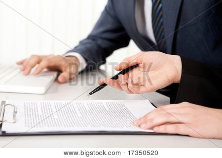 Female hands with a pen over contract