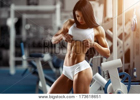 poster of Fitness woman showing abdominal muscles. Bodybuilder motivation. Perfect female sports figure. Fitness woman posing in the gym. Fitness photo shoot in the gym. Fitness bikini