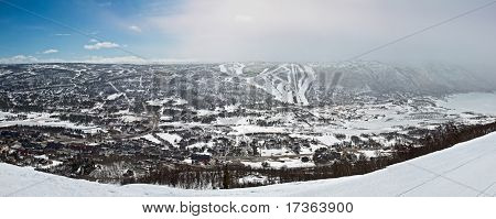 Panoramic View Of Small City In The Valley With Winter Mountain Slopes And Ski Routes