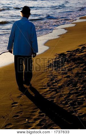 Old Man Walking On The Beach.