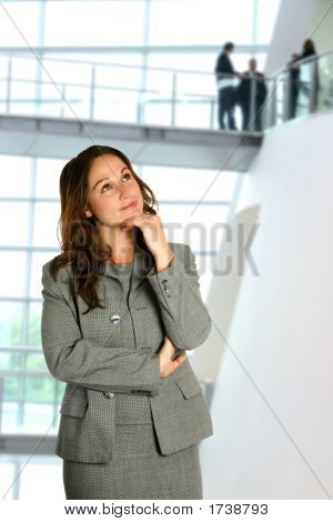 Thinking Businesswoman In Corporate Interior