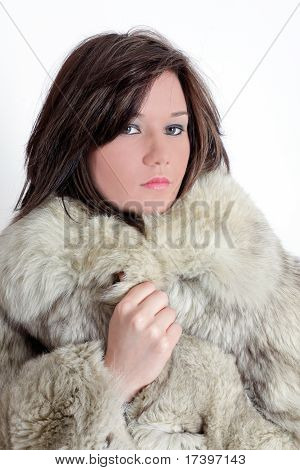 Portrait of a young brunette russian teenager girl with fur in studio