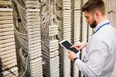 Technician using digital tablet while analyzing server in server room poster