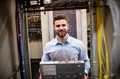 Portrait of technician removing server from rack mounted server in server room poster