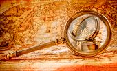 Vintage still life. Vintage magnifying glass lies on an ancient world map in 1565. poster