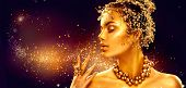 Gold Woman make up with golden shiny skin. Beauty fashion model girl with golden make up, hair and j poster
