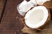 Coconut With Coconut Oil In Jar On Wooden Background poster