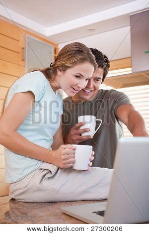 Portrait of a young couple having tea while using a laptop in their kitchen