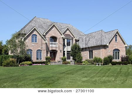 Large brick home with arched entry and front balcony