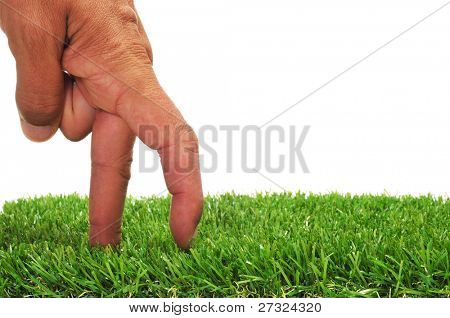 a man hand with its fingers simulating someone walking or running on the grass