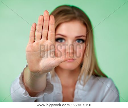 Young attractive women holding hand in front of camera showing a sign STOP