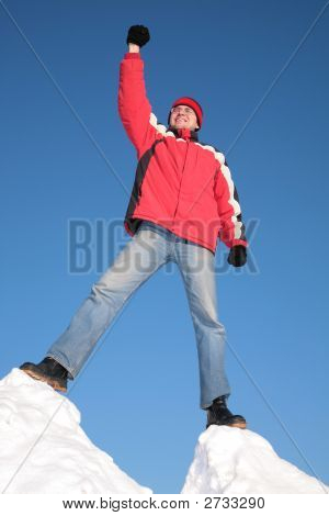 Man In Red Jacket On Top Of Snow Hill With Hand Up