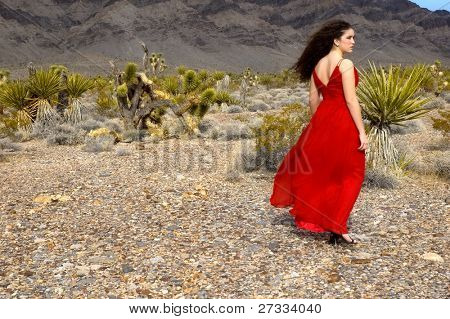 A girl walking in the desert wearing a red silk evening gown and stilettos