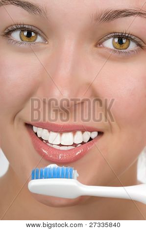 Teenage girl with beautiful white teetn brushing her teeth