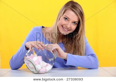 Gourmand woman eating marshmallows