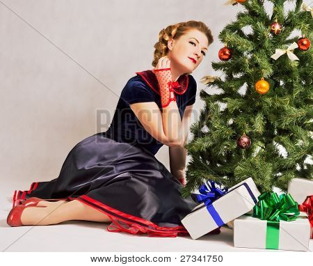 Woman next to Christmas tree