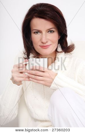 Attractive smiling middle-aged woman in knitted pullover sitting on the armchair with cup in hands, over white wall