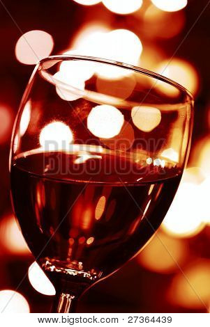 close-up of wineglass with abstract lights background