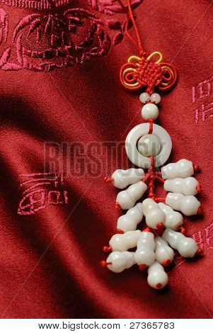 Cluster of jade accessories on Jin-Silk background.lucky knot pray the safety and property for the owner.