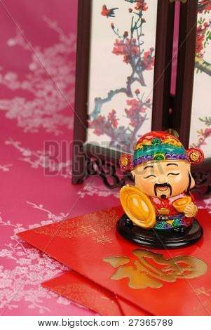 Traditional mammon figure with red envelope and screen on festive background.