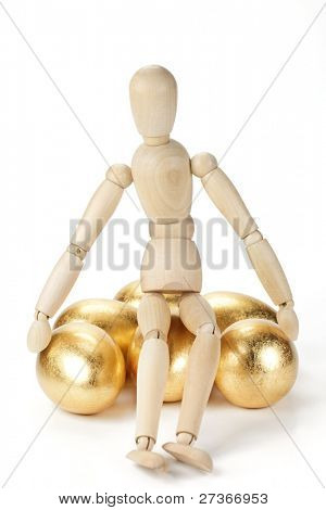 Wooden mannequin and gold egg,Monetary concept