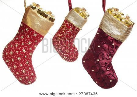 Christmas stocking with gift box hanging over white background.