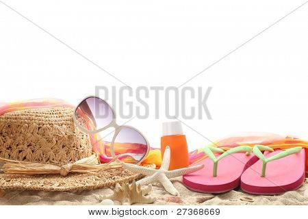Beach accessories with straw hat,sun glasses,shawl and flip flops on sand.