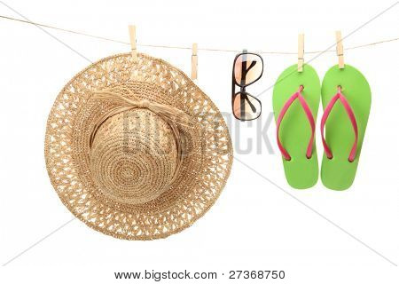 Straw hat,sunglasses and flip flops hanging on  clothes line.
