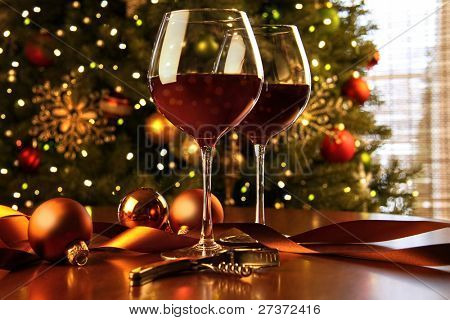 Red wine on table Christmas tree in background