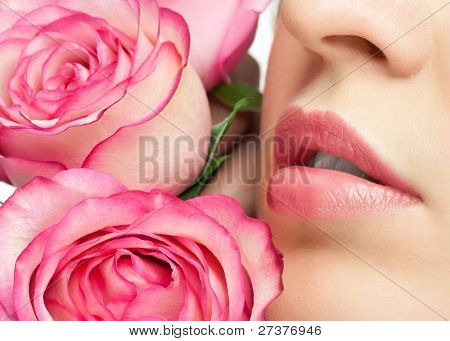 Close-up of woman beautiful lips with pink roses