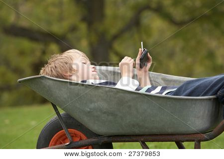 Young Boy Laying Wheelbarrow Using Smart Mobile Phone