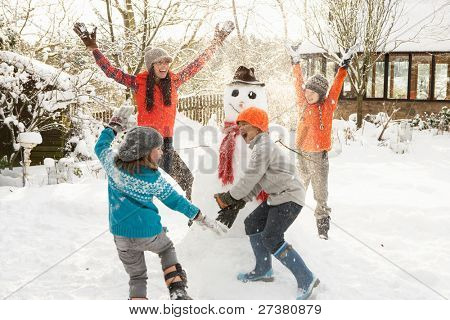 Mother And Children Building Snowman In Garden