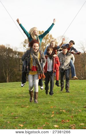 Group Of Teenage Friends Having Piggyback Rides In Autumn Landscape