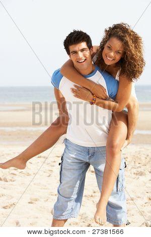 Pareja joven romántico superpuesto divirtiéndose en la playa