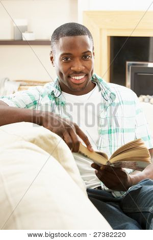 Young Man Relaxing Sitting On Sofa Reading Book At Home