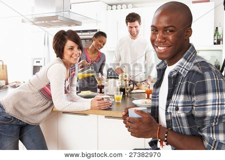 Group Of Young Friends Preparing Breakfast In Modern Kitchen