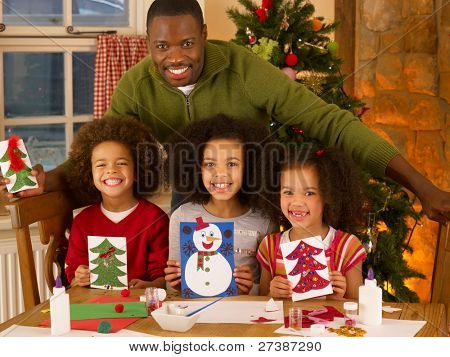 African American father making Christmas cards with children