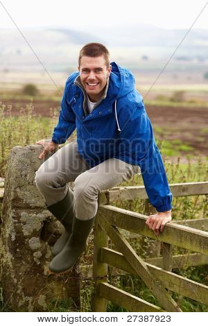 Man jumping over country gate