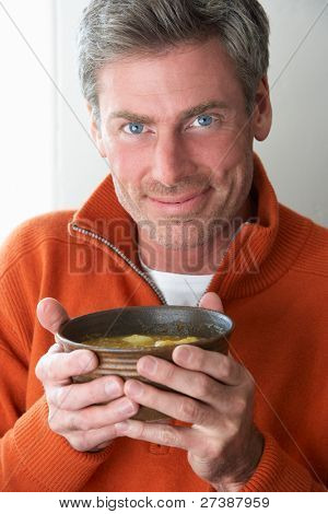 Man holding bowl of soup