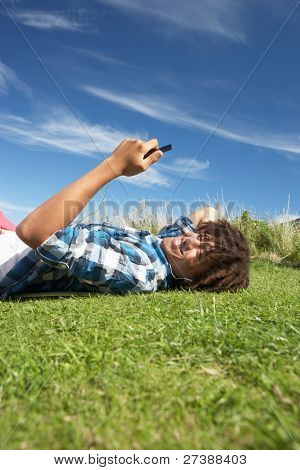Teenage boy lying on grass with phone