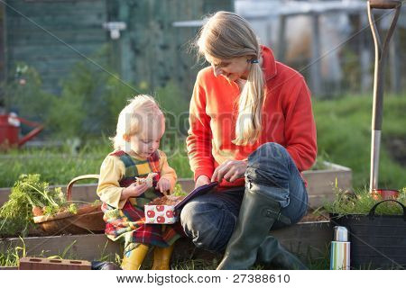 Woman and child with picnic on allotment