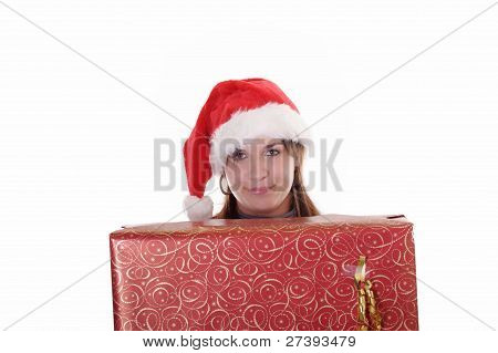 Young Woman With Christmas Hat Behind A Big Present