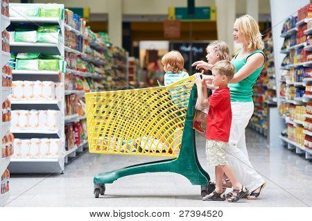 mujer y niños con carrito de la compra en el supermercado, tienda warwehouse