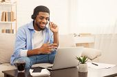 Smiling African-american Guy In Headphones Studying Foreign Language Online Through Video Conference poster