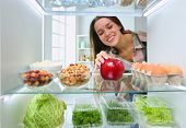 Portrait Of Female Standing Near Open Fridge Full Of Healthy Food, Vegetables And Fruits. poster